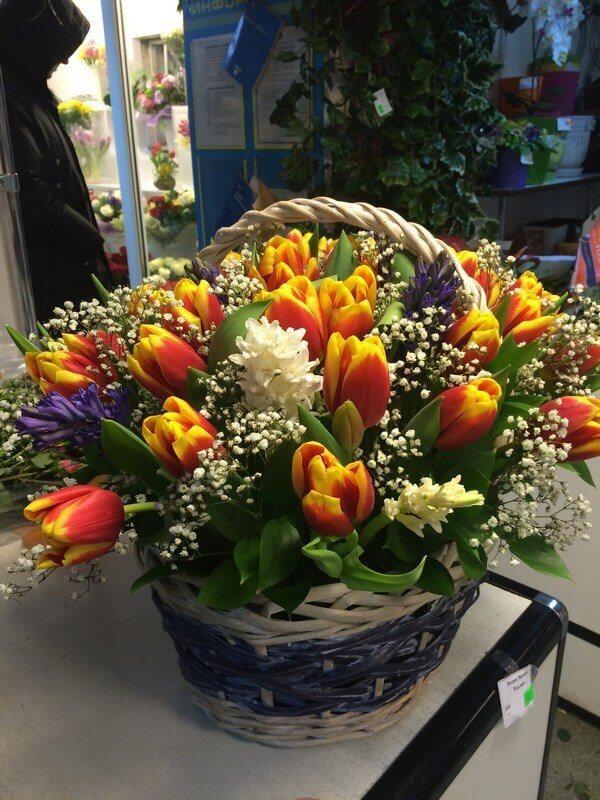 Корзина с желто-оранжевыми тюльпанами и декоративной зеленью