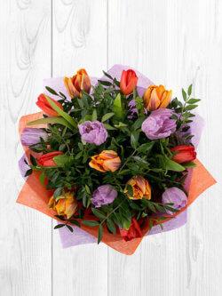 Букет из 15 тюльпанов с декоративной зеленью в упаковке из фетра