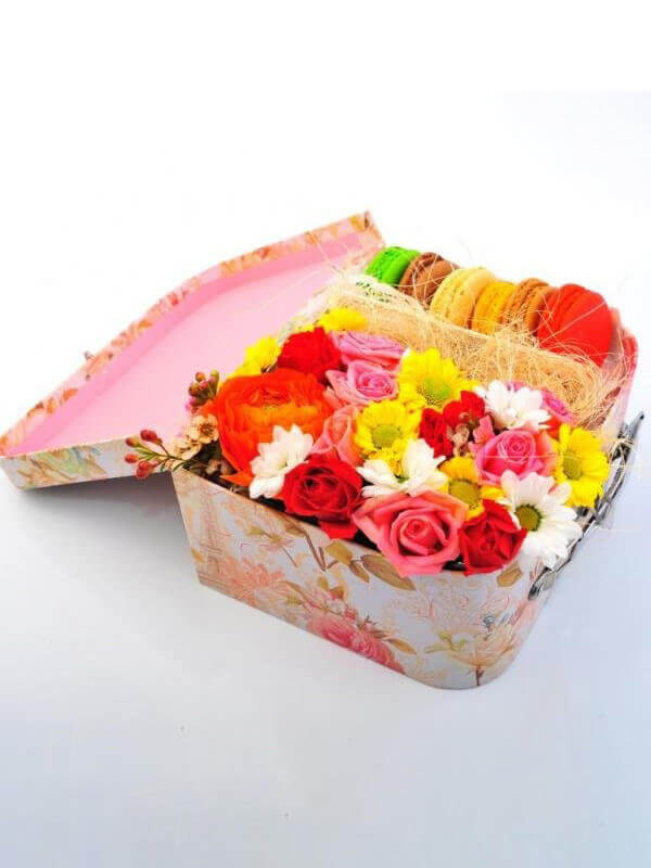 Композиция чемодан с цветами и макарунами