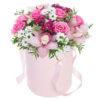 Шляпная коробка с розовыми орхидеями, розами, хризантемами и декоративной зеленью.