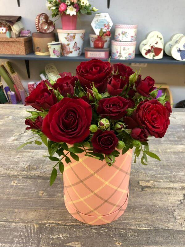 Шляпная коробка с красными розами и декоративной зеленью