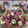 Корзина с хризантемами, кустовыми хризантемами, розами и декоративной зеленью.
