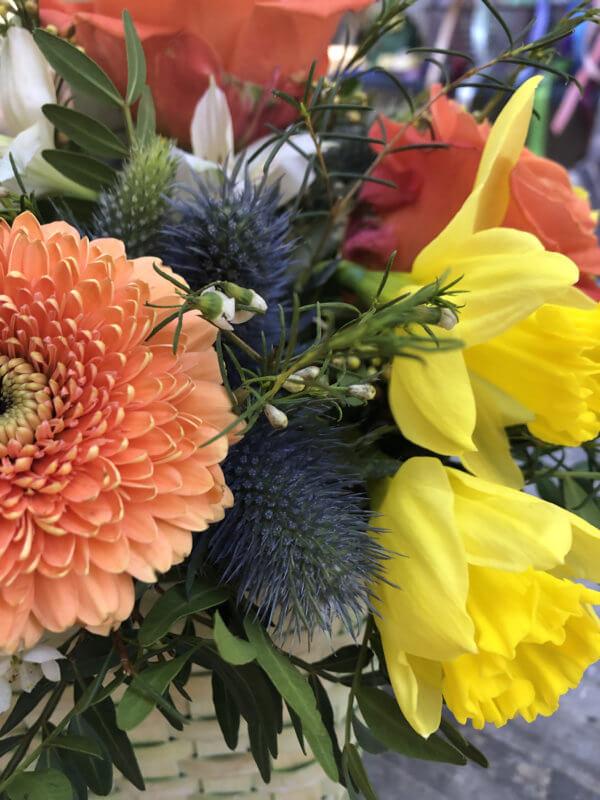 Корзинка с оранжевыми хризантемами, розами, тюльпанами, хризантемами и декоративной зеленью