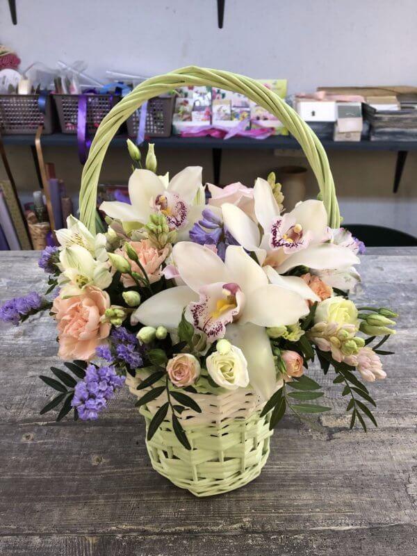 Плетеная корзинка с орхидеями , кустовыми розами и декоративной зеленью