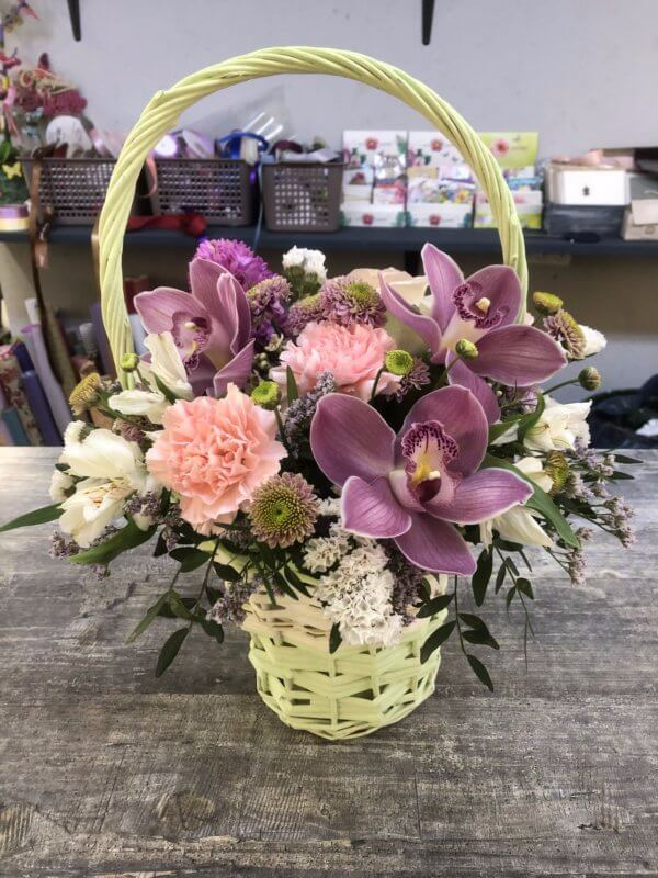 Плетеная корзинка с фиолетовыми орхидеями, гвоздиками, альстромерями, хризантемами и декоративной зеленью