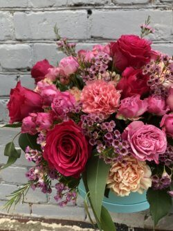 Шляпная коробка с розами, диантусом, кустовыми розами, хамелациумом и зеленью